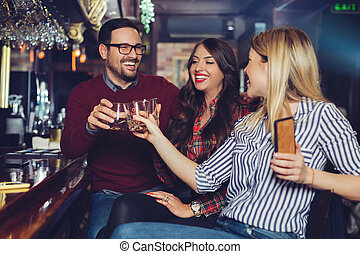 Friends got together after work in a bar for a few drinks.