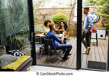 Friends grilling food and enjoying barbecue party outdoors