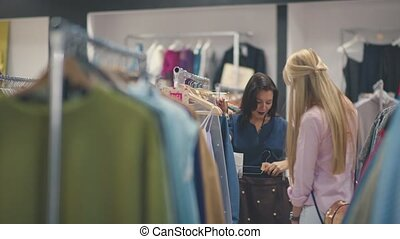 Friends happily shopping in clothing store. Clothing on hangers