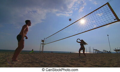 Friends have fun playing beach volleyball during summer holidays