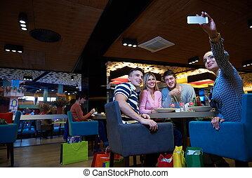 friends have lanch break in shopping mall, eating italian...