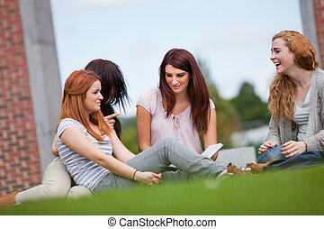 Friends having a good time while sitting on the lawn