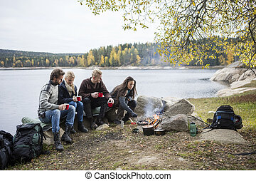 Friends Having Coffee While Woman Cooking On Campfire -...