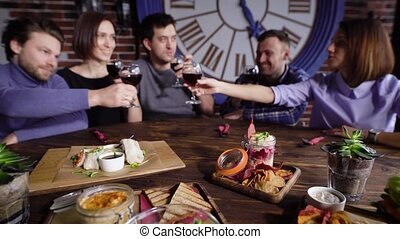 Group of people gathering together at dinner having meal and drinks in restaurant.
