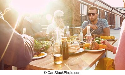 friends having dinner or bbq party on rooftop - leisure and...