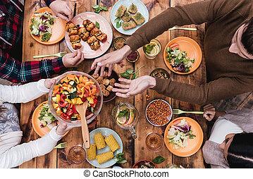 Friends having dinner. Top view of four people having dinner...