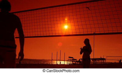 Friends having fun play beach volleyball at sunset