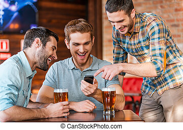 Friends having fun. Three happy young men in casual wear drinking beer in pub while one of them pointing smart phone and smiling