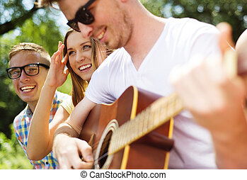 Friends having fun with guitar - Group of happy friends with...