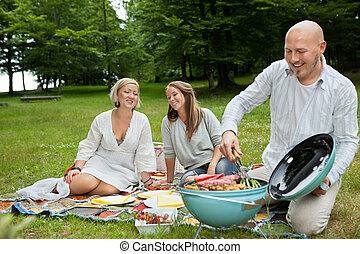 Friends Having Meal At An Outdoor Picnic - Happy Caucasian...