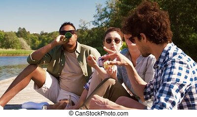friends having picnic on pier at lake or river - leisure and...
