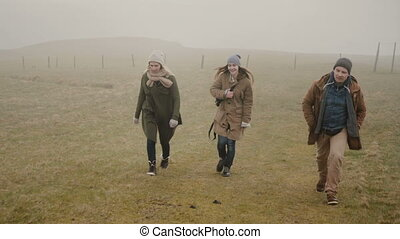 Friends hiking together in foggy day. Two woman and man...