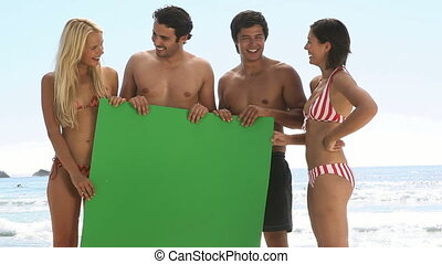 Friends holding a green board on th
