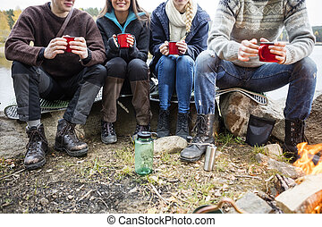 Friends Holding Coffee Cups At Campsite