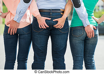 Friends Holding Each Other's Buttock - Rear View Of Friends...