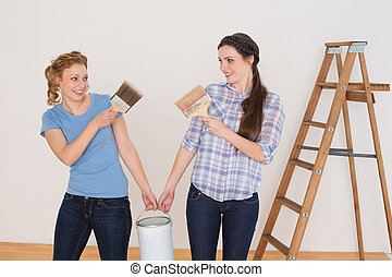 Friends  holding paint brushes and can in a new house