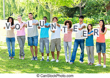 Friends holding placards spelling volunteer - Full length of...