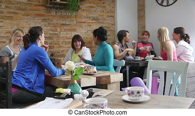 Friends In A Cafe - Women are in a cafe, scoialising over...