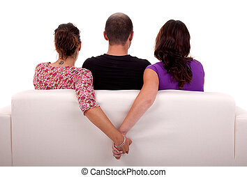 friends in a couch, with two girls given hands, isolated on white background. Studio shot