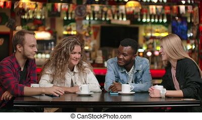 Friends in a restaurant tell each other stories and their...