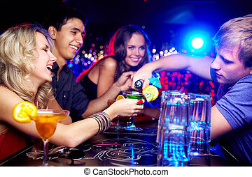 Friends in bar - Image of happy girl looking at her glass...