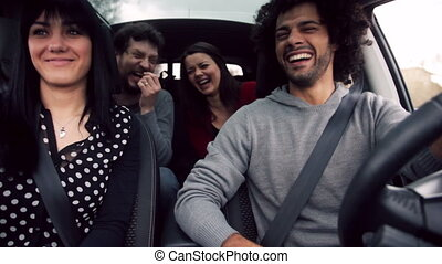 Friends in car having lot of fun - four cool people having...