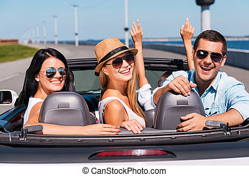 Friends in convertible. Group of young happy people enjoying road trip in their convertible while three of them looking over shoulder and smiling
