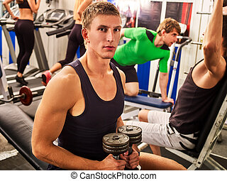 Friends in gym workout with fitness equipment. Training men.