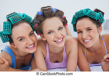 Friends in hair rollers and pajamas lying in bed and smiling...