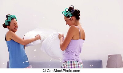 Friends in hair rollers having pillow fight at home at...