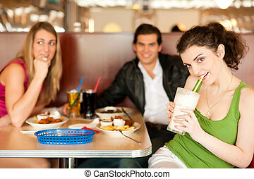 Friends in Restaurant eating fast food - Three friends in a ...