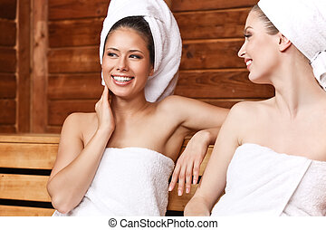 Two beautiful laughing females sitting and talking in sauna