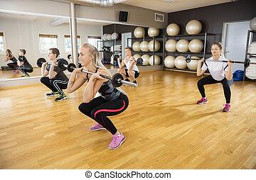 Friends Lifting Barbells In Fitness Club