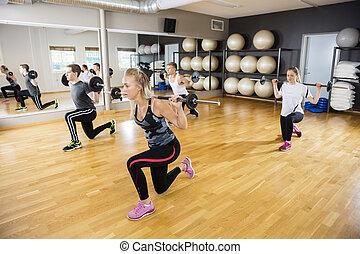 Friends Lifting Barbells On Hardwood Floor In Gym