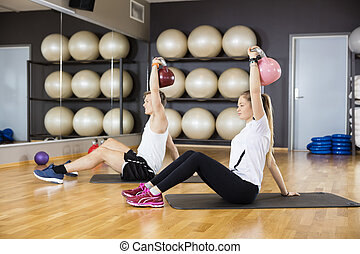 Friends Lifting Kettlebells While Sitting On Mat In Gym