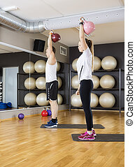 Friends Lifting Kettlebells While Standing On Mat In Gym