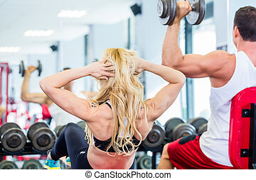 Friends lifting weights in fitness gym
