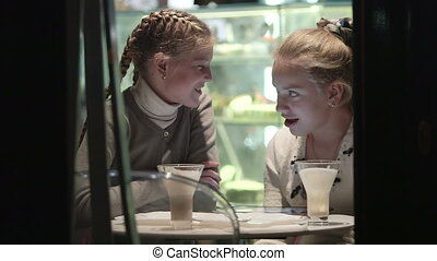 Friends light conversation at coffee shop view through night window