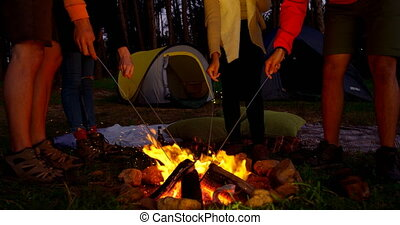 Friends lighting sparklers on campfire in the forest 4k - ...