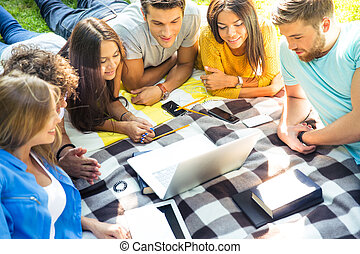 Friends looking at laptop outdoors - Portrait of a young...