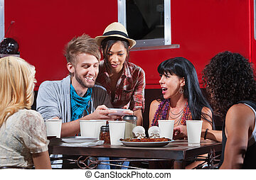 Friends Looking at Text Messages - Friends eating out and...