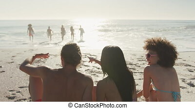 Friends looking at the view with surfboarders - Rear view of...