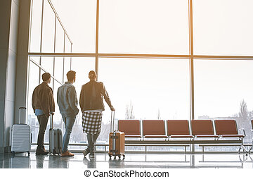 Friends looking at window in airport