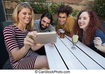 Friends looking their photos on mobile phone in bar