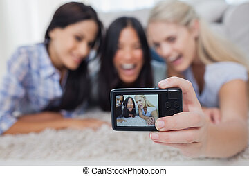 Friends lying on floor and taking a self picture at home in...