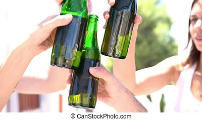 Friends making a toast with beer bottles - Close-up of ...