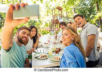 Friends making selfie photo in outdoor restaurant - Portrait...