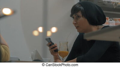Friends meeting in cafe. Woman talking and using cellphone