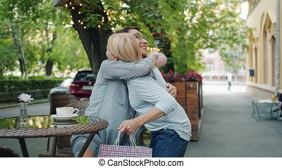 Friends attractive mature women are meeting in street cafe hugging looking inside paper bags with purchases discussing shopping day. People and lifestyle concept.