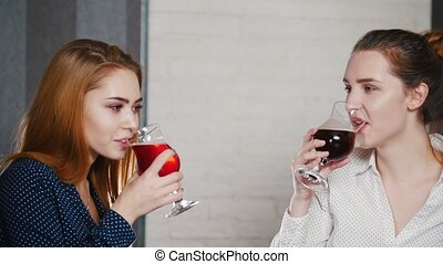 Friends met at the bar. Two young women drink cocktails and talk.